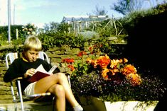 Photograph of a boy reading a book outside.