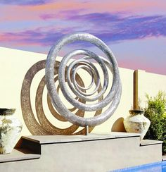 Contemporary stainless steel sculpture that enhances residential swimming pool