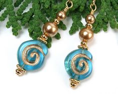 These sweetly stylish dangles feature the symbol of the spiral and are made with aqua blue Czech glass beads and Swarovski gold pearls. The Czech