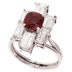 Diamond Ruby Platinum Ring. Elegant vintage ring is made in fine platinum and features a vivid sparkling red 6.0mm x 6.5mm faceted oval ruby of a about 1.08 carats surrounded by an estimated 3.90 carats of E-F color VVS clarity emerald-cut diamonds. U.S. 1980s $8,400