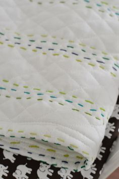 A Quilt For The Bun | Young House Love -  i like the ease of using the diamond quilted fabric but i think i would add contrast binding to the edge instead of just hemming it.