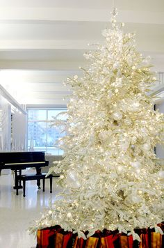 A stunning white Christmas tree is effortlessly modern and pronounced when red metallic gift bags are placed underneath.