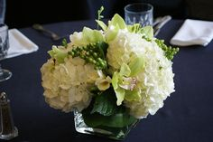 Simple centerpiece arrangement of hydrangeas, cymbidium orchids, hypericum berries, and freesia, with a green aspidistra leaf tucked inside the vase for a sleek finish. Created by Anastasia Ehlers. Green Hydrangea Centerpieces, Hydrangea Bouquet, Simple Centerpieces, Hydrangeas, Simple Wedding Bouquets, Wedding Flowers, Flower Decorations, Wedding Decorations, Wedding Ideas