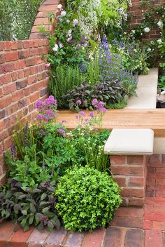 Patio plantings of fragrant herbs and flower garden next to brick wall, with built-in garden bench - sit next to scented plants!