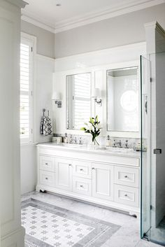 Classic white bathroom with subtle patterned floors and elegant details.