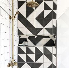 Black Alalpardo tiles from Bert and May create a stunning backdrop to the brass facets in this unique shower room