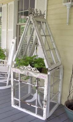 Mini Greenhouse made from six old windows-so clever! It is the star of this front porch.... This would be cute for your herb garden of to have out next to a little tea table and chairs !!