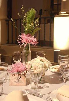 Centros de mesa con recipientes antiguos, en diferentes alturas y arreglos florales silvestres.