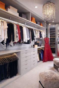 Monique Lhuillier - Grey walk-in closet features a wall of floor to ceiling gray built-ins boasting a top shelf filled with gray and orange boxes stacked above a long clothes rail and a built-in dresser with a glass display top illuminated by a crystal drops chandelier.