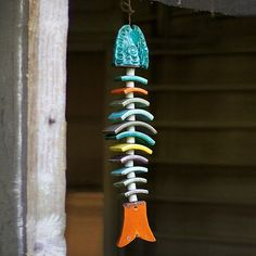 Vivid colors contrast with a stark fish skeleton design for a striking piece. Hang this wind chime up outside by your garden or backyard door or indoors by a window.