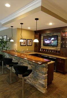 The stone is the perfect finish to this basement bar, complete with a mounted flatscreen!  #basement #bar   http://bedroom-gallery2.blogspot.com