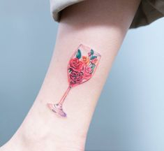 Floral wine glass tattoo on the ankle.