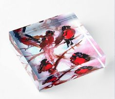 My red robins are all fluffed up against the cold. Now my adorable watercolor painting of this snowy winter scene is available as a print inside an acrylic block.  An original gift that will delight adults and children alike.  Features:  - Vibrant back mounted photographic prints - 1 (2.5 cm) thick solid free-standing acrylic block for desk, table top or shelves - Diamond cut sides provide a sharp image from any angle - Hand polished for a crystal clear finish - Available in 4×4 (10×10 cm)…