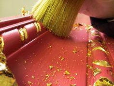 Decorazione foglia oro su incisioni di cimasa colore lampone...