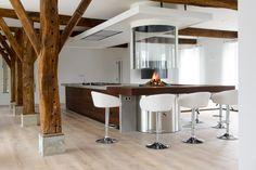 Keukeneiland met betonnen werkblad van 6 meter lang. Met Pitt Cooking en vrijhangende glashaard van Boley. Keuken maatwerk Teawood van JP Walker #keuken #haard