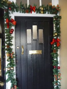 #Pinegarland decorating a #door. #Garland has #red and #tartan #bows, red and #gold #baubles, and #pine #cones. Pine Garland, Christmas Arrangements, Christmas Flowers, Table Centers, Pine Cones, Tartan, Bouquet, Bows, Wreaths