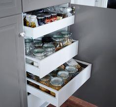 Porte ouverte laissant entrevoir trois tiroirs contenant des bocaux en verre