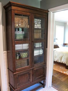 Clever Storage Ideas - here an old leaded glass cabinet provides a place to store linens in a bathroom - via Decorology