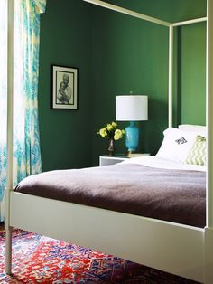via Kim Jeffery Photography. With white walls, colorful pillows, a bright green throw with large tassles and bright colorful art work.