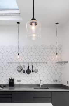 Tiles, concrete work surface and matt black cabinets.