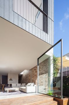 A dramatic pivoting glass door protrudes from the monolithic extension conceived by Australian practice Marston Architects for the renovation project of this single family house in Sydney