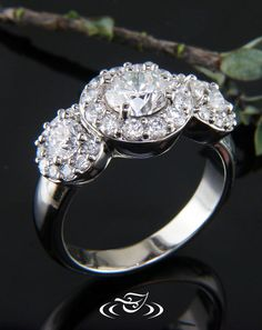 Custom 14kt white gold three stone high polish halo mounting to hold 4-prong set 1.01 ct round brilliant cut center diamond. Prong set round brilliant cut side stones. 3 Bead set halos with round brilliant cut accent diamonds. Dome profile & tapering round shank.