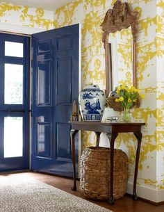 Yellow and blue foyer design with yellow chinoiserie wallpaper and glossy blue cobalt blue front door. Antique console table with cabriolet legs with Chinese ginger jar and woven basket. Antique wood mirror over foyer table and cheetah foyer rug.
