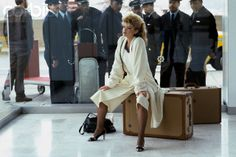 Model Kelly Emberg seated on a suitcase in an airport waiting area, being watched by airline pilots, wearing an ivory knit coat over a black lace-collared ivory pullover and an ivory wool jersey culotte skirt, all by Sonia Rykiel, with shoes by Mario Valentino.1982