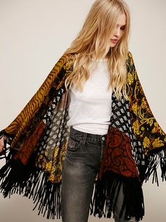 Drapey kimono featuring a gorgeous bohemian mixed print and cool suede fringe accents. Sheer fabrication.