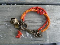 Orange coco and old Indonesian glass beads  Red seed beads and coral drops  Coco ring  Charm: brass jingle bell (Nepal), brass circle dot and coral beads  Brass components  Length 18 - 21 cm / 7,1 - 8,3 inches  The jingle bell makes sound!