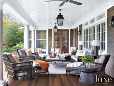 Light fixtures by Paul Ferrante illuminate a porch with ample seating thanks to Palecek's sturdy pieces, which are covered in boldly striped Sunbrella fabric. The coffee table was from the owner's previous house and refinished for outdoor use.