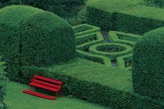 red bench in a green garden