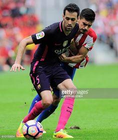 Barcelona's midfielder Sergio Busquets vies with Sporting Gijon's midfielder Sergio Alvarez during the Spanish league football match Real Sporting de...