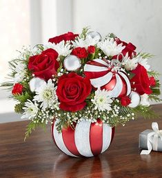 EXCLUSIVE All the sweetness of the holiday season is captured in our limited-edition arrangement. Joyful red & white blooms are gathered with festive silver ball ornaments and arranged inside our peppermint candy container. With its sparkling candy cane-stripe design and matching lid, it's a keepsake piece they'll love to reuse throughout the year…and for years to come. Arrangement of red roses and mini carnations; white cushion poms; accented with baby's breath, assorted Christmas greenery Christmas Flower Arrangements, Christmas Greenery, Christmas Flowers, Christmas Centerpieces, Christmas Themes, Floral Arrangements, Christmas Crafts, Christmas Decorations, Christmas Wine