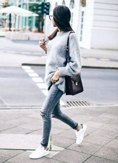 A gray sweater pairs well with darker gray jeans, white sneakers, and a shoulder bag