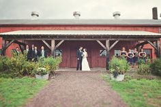 Wedding party portrait at Quonquont Farm. Standing in front of one of the three barns on the property. This barn houses the farm stand.