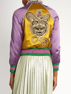 Gucci Embellished duchess-satin bomber jacket  AW16 collections are filled with various incarnations of the classic bomber jacket. Gucci's gold duchess-satin version is detailed with contrasting metallic-green and pink Web-striped panels, purple sleeves, and sky-blue piping. Completing the eclectic picture is an embroidered Western Tiger appliqué – it takes around five hours to create.