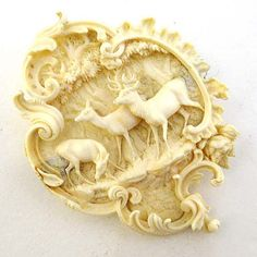 """Ivory : a Victorian German / Swiss carved brooch depicting three deer ( including one Stag ) within a wood , bordered with a Rococo C Scroll edge, has associated safety chain. 2 7/8"""" high."""