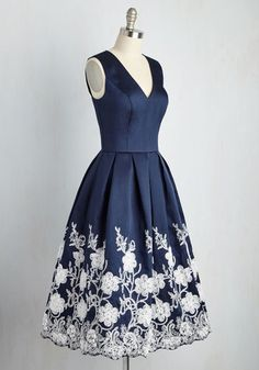 From the moment you slip into this navy blue dress by Chi Chi London, the ballroom will turn from walkway to runway! Confidently strut in the princess-seamed bodice and chiffon floral appliques - supported by silver, beaded stems - and this pleated midi will make any event a fashionable affair.