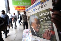 A Kenyan man reads a newspaper on June 25, 2013 in Nairobi with the front page carrying a headline concerning Nelson Mandela being in a critical condition in hospital South Africa.