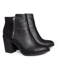 Black. Ankle boots in imitation leather with visible side zip and rubber soles…
