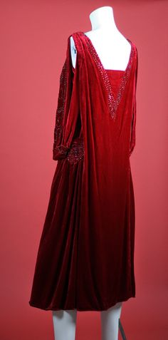 1920's Dress Truly one of a kind! Rare beaded red silk velvet flapper dress. Lined with fabric that feels like silk. Sophisticated draped front, shoulder criss cross bands, medallion style beading at the hips. There are no labels present but I wouldn't be surprised if this was a labeled garment.