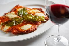 """""""Chicken Parmigiana."""" Breaded flattened chicken breast -- topped with melted mozzarella, smothered in home-made tomato sauce. Finished with grated Parmesan."""