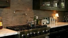 Jeff Lewis Design- Stainless steel appliances, stainless steel pot filler, brown beige gray mini-subway tiles, dark kitchen cabinets, glass-front kitchen cabinets, white carrara, marble countertops, oil-rubbed bronze pulls knobs hardware. (not a fan of the carrara countertop here, but like the cabinet/backsplash/stainless combo)