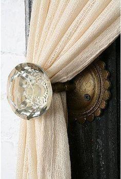 Cute door knobs as curtain tie backs.