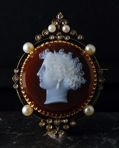 A fine oval agate cameo, with two layers (red cornelian and white calcedony) of very good carving, depicting the nymph Arethusa. The representation is inspired by the obverse side of a famous coin from the greek city of Syracuse in Sicily.The cameo is set in a nice gold brooch, enhanced with natural pearls and rose-cut diamonds. Perfect condition. France, circa 1860.