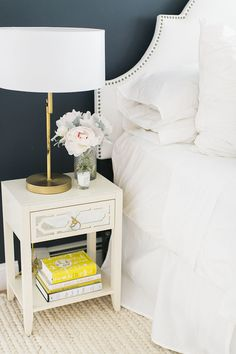 blue walls, upholstered bed with nailhead trim, mirrored drawer nightstand with brass table lamp