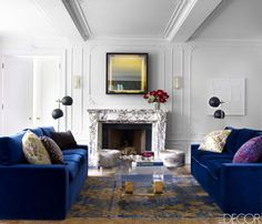 The living room features custom-made sofas, upholstered in a velvet by Rose Cumming, 1950s Swedish floor lamps, a 1960s cocktail table, and a neon work by Iván Navarro over a Louis XVI marble mantel; the vintage sconces are by J.T. Kalmar, and the antique rug is Persian.   - ELLEDecor.com