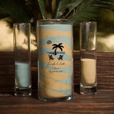 Unity Sand Vase Set includes a large glass vase and two smaller glass pouring vases. The large vase can be customized with a logo design or monogram in your choice of ink color to match your wedding theme.