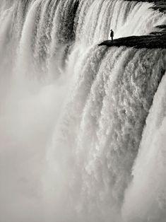 Contemplative Man Stands Over Massive Waterfall by Dimitar Variysky